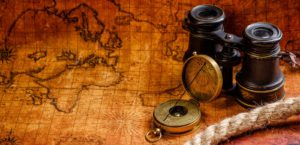 Old Binoculars, Compass and Rope on Top of Rustic Map