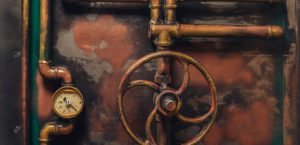 Rusted Boiler Room Pipes with Pressure Gauge and Wheel